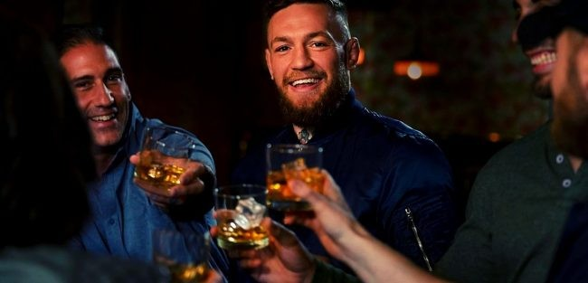 Conor holding proper 12 whiskey on glass