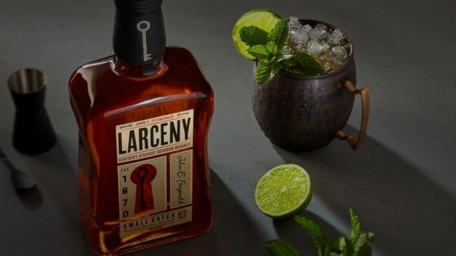 Larceny 92 proof bourbon on glass with lemon and ice on side