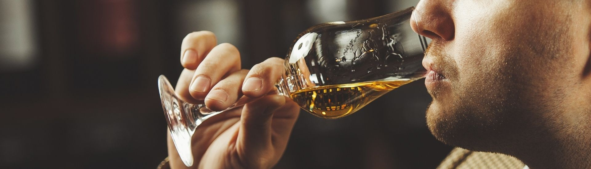 Man tasting whiskey from glass